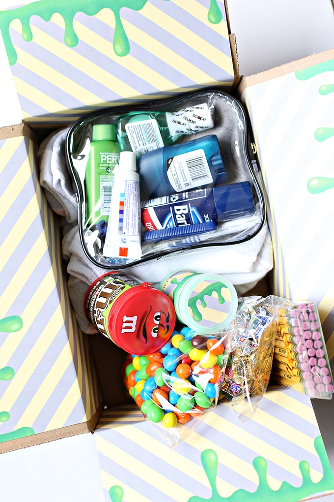 m&ms, plastic bags of candy, pack of pencils, toiletry bag with toothpaste, shampoo, shaving cream, deodorant, and mouthwash in it, all in a a cardboard box decorated to look like ghostbusters green slime