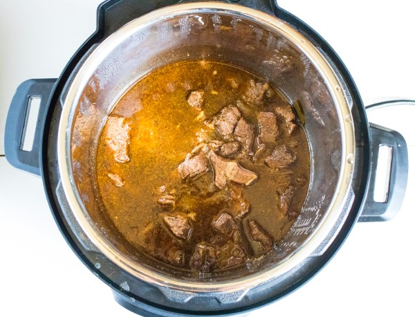 overhead view of beef barbacoa in sauce in an instant pot on a white background