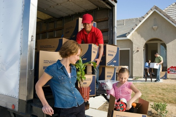 a mom, daughter, and a mover, moving boxes from a moving truck with another child and a dad in front of the house in the background