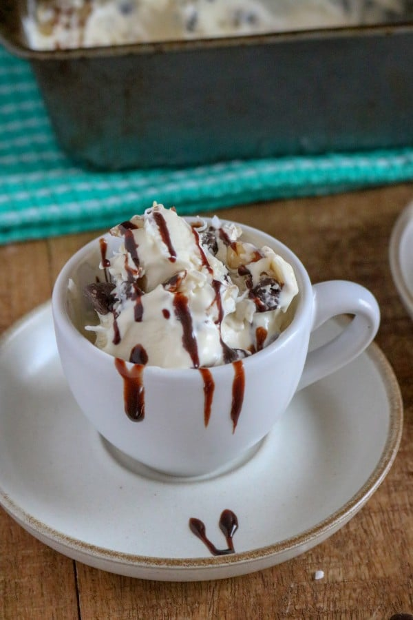easy homemade almond joy ice cream in a white mug on a saucer on a brown table with more ice cream in a pan in the background