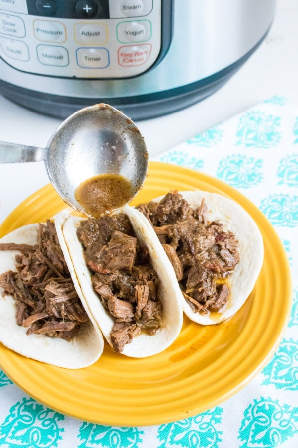 a metal spoon pouring sauce over beef barbacoa in three flour tortillas topped with green garnish and chopped tomatoes on a yellow plate on a green and white cloth with an instant pot in the background