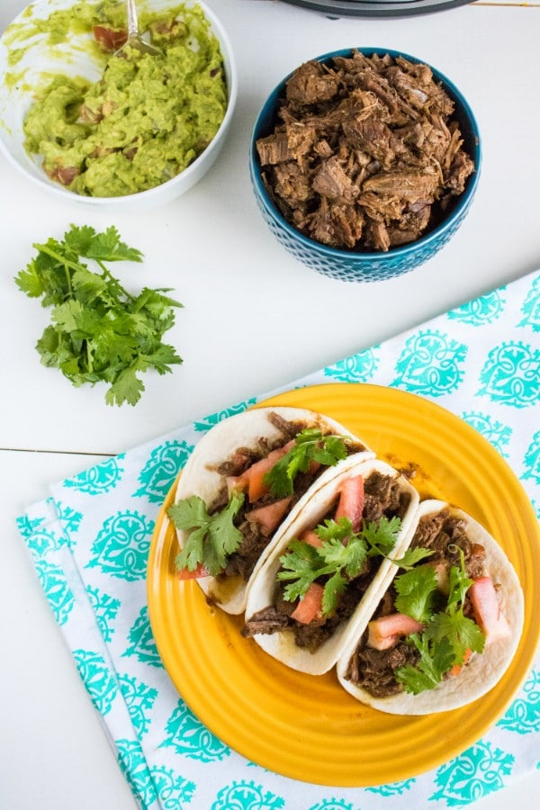 an overhead view of beef barbacoa in three flour tortillas topped with green garnish and chopped tomatoes on a yellow plate on a green and white cloth with a blue bowl full of bee, a white bowl of guacamole and an instant pot in the background