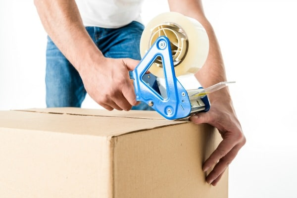 a man putting packing tape on a cardboard box with a white background