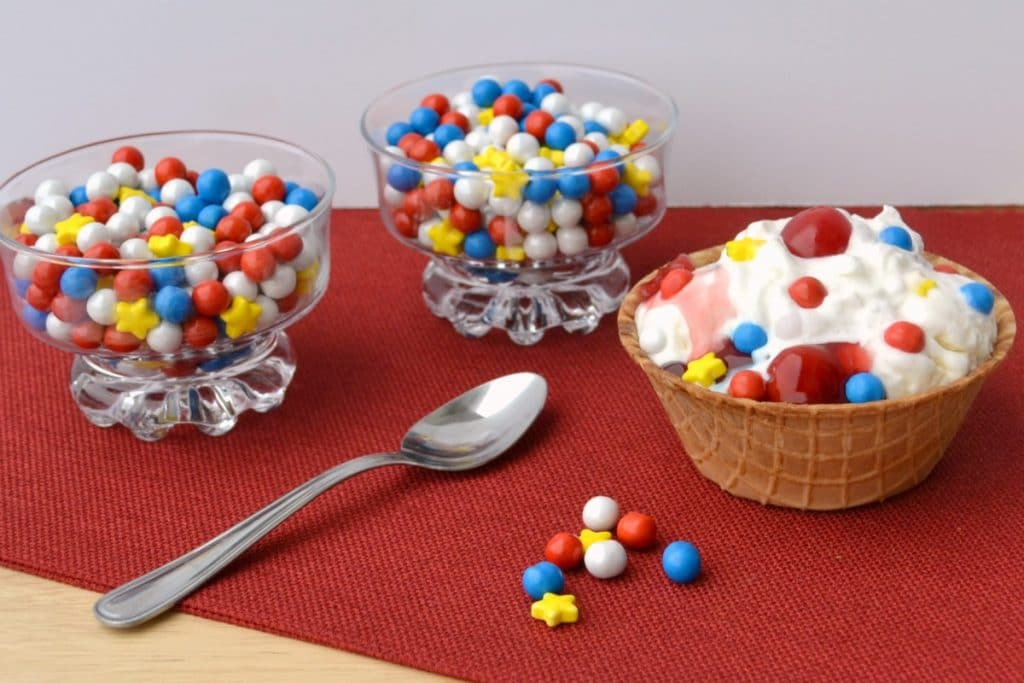 vanilla ice cream topped with red, white and blue round candies, yellow candies, and cherries in a waffle bowl next to two glass of candy and a spoon on a red cloth