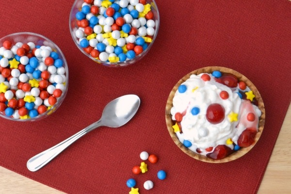 vanilla ice cream topped with red, white and blue round candies, yellow candies, and cherries in a waffle bowl next to two glass bowls of candy and a spoon on a red cloth
