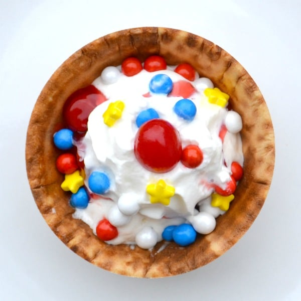vanilla ice cream topped with red, white and blue round candies, yellow candies, and cherries in a waffle bowl on a white background