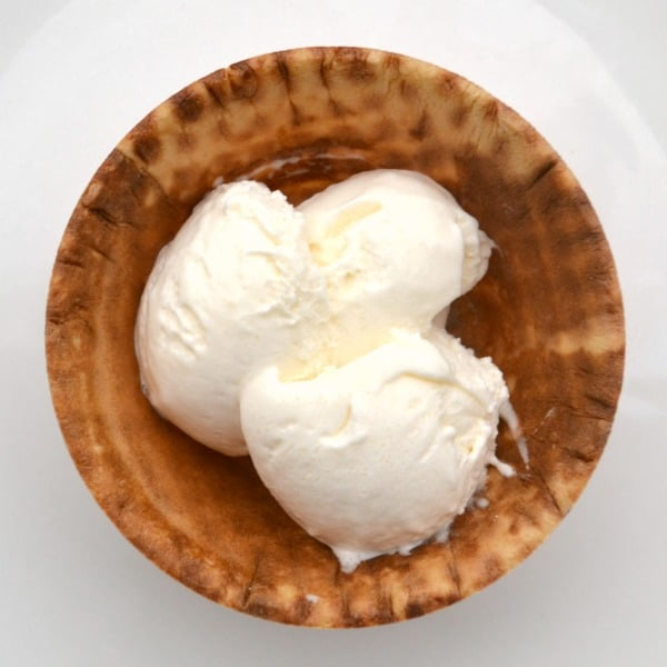 vanilla ice cream in a waffle cone bowl on a white plate