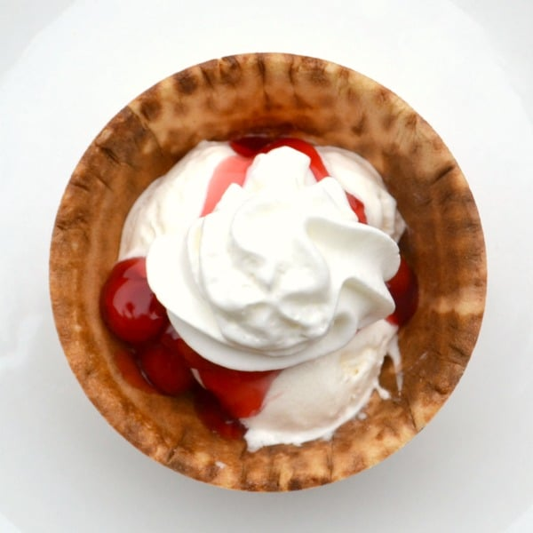 vanilla ice cream topped with cherry pie filling and whipped cream in a waffle cone bowl on a white plate