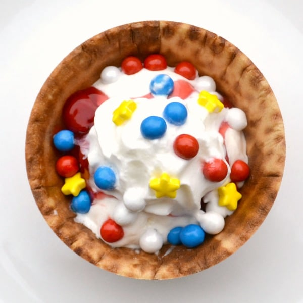 vanilla ice cream topped with red, white and blue round candies, yellow candies, and cherries in a waffle bowl on a white plate