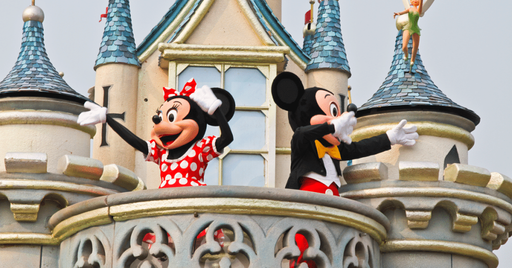 Minnie and Mickey Mouse standing on the balcony of a Disney castle