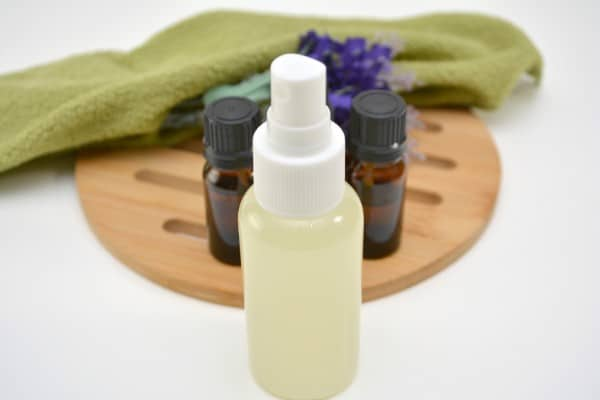 DIY Poo Pourri Spray in a plastic spray bottle on a white table with a wooden trivet, bottles of essential oils and a green cloth in the background