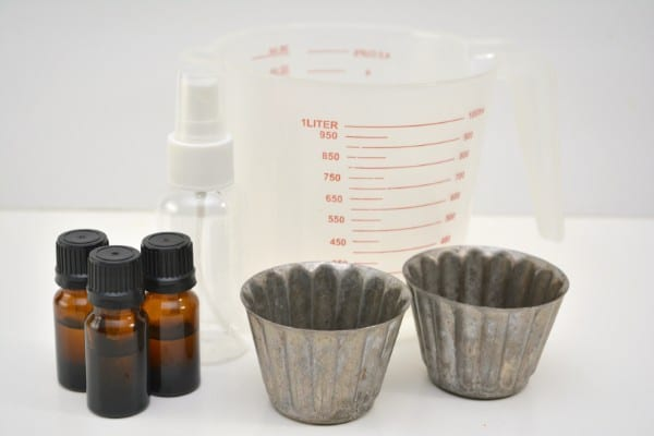 bottles of essential oils, metal cups, plastic spray bottle, measuring cup on a white table