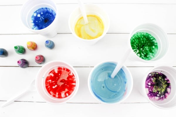 plaster of paris, water, different colors of food coloring in plastic cups on a white wood table