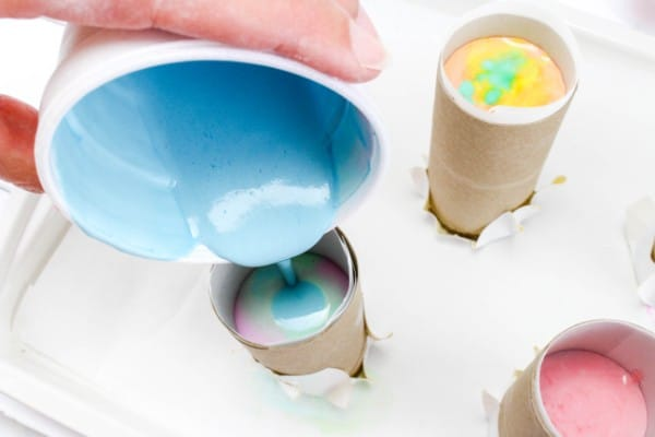 a hand pouring colored plaster of paris into a toilet paper roll with more filled rolls in the background