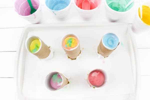 plastic cups with remnants of colored plaster of paris, and toilet paper tubes filled with colored plaster of paris on a white tray on a white wood table