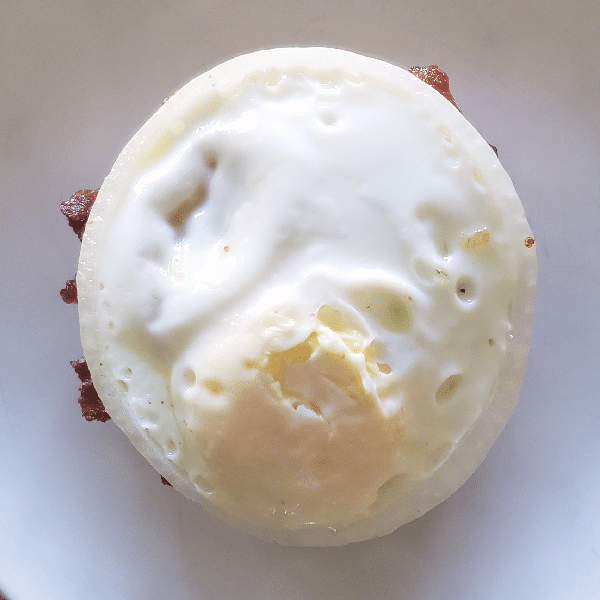 a cooked egg in the center of an onion on top of a uso burger on a white background
