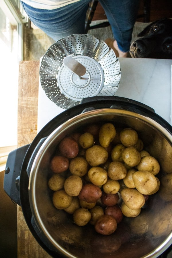 overhead view of potatoes in an instant pot next to a steamer basket