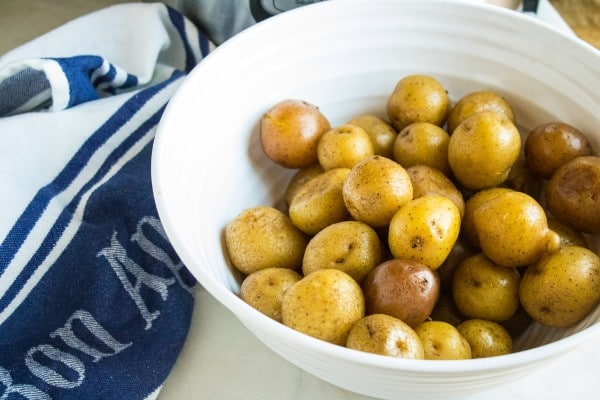 potatoes in a white bowl on a white counter next to a blue and white cloth