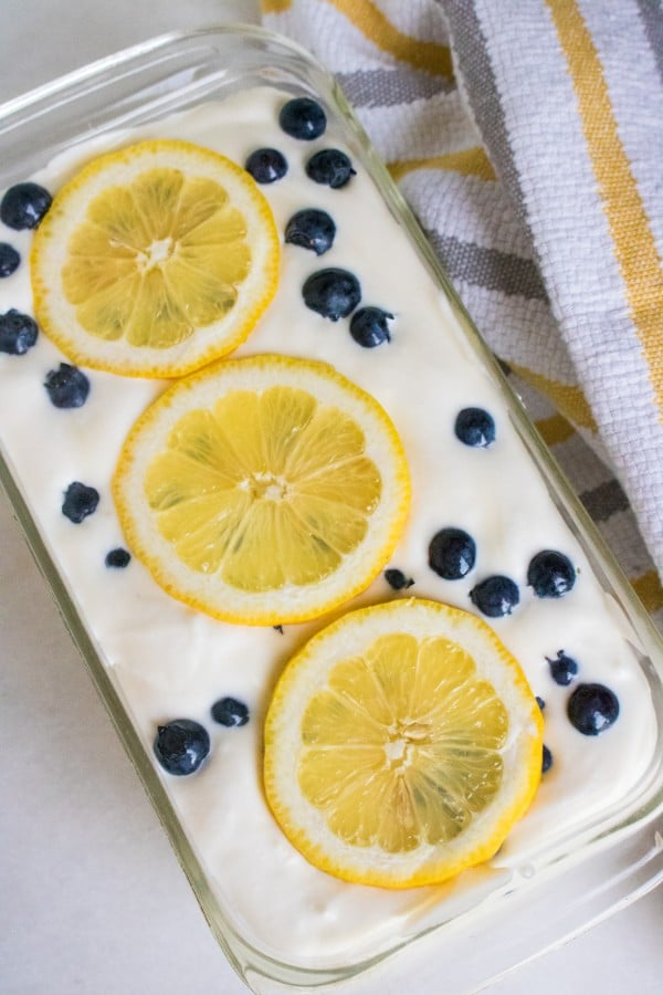 ice cream mixture topped with blueberries and lemon slices in a glass dish on a white counter next to a white, yellow and gray linen