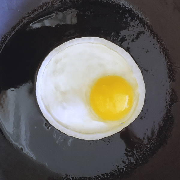 an egg cooking in the center of an onion slice in a frying pan
