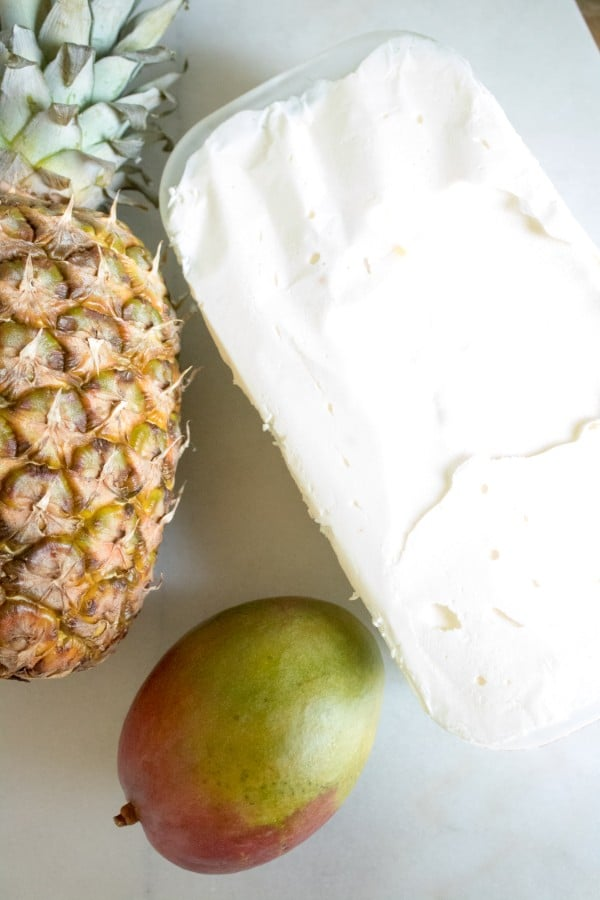 ice cream in a freezer safe container on a counter next to a pineapple and a mango