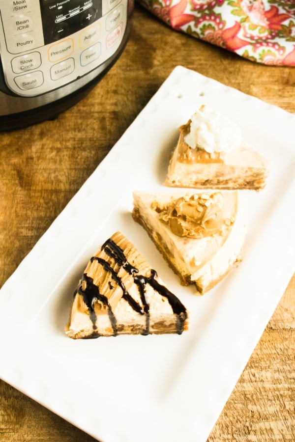 overhead view of slices of peanut butter cheesecake on a white plate on a brown table with an instant pot and a cloth in the background