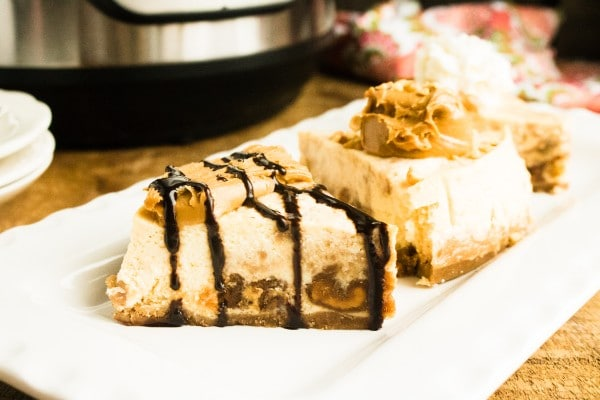 slices of peanut butter cheesecake topped with chocolate sauce and peanut butter on a white plate