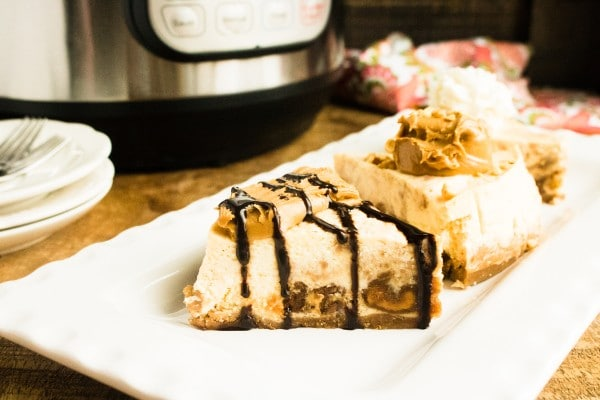 slices of peanut butter cheesecake on a white plate on a brown table with an instant pot, plates and forks, and a cloth in the background