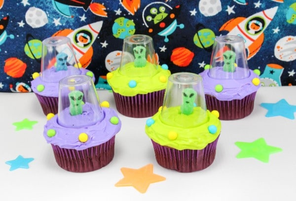 five cupcakes decorated with green or purple frosting, round candy, a gummy candy with eyes and a mouth drawn on with a plastic cup around it, on a white table with colored stars on it with a space scene in the background