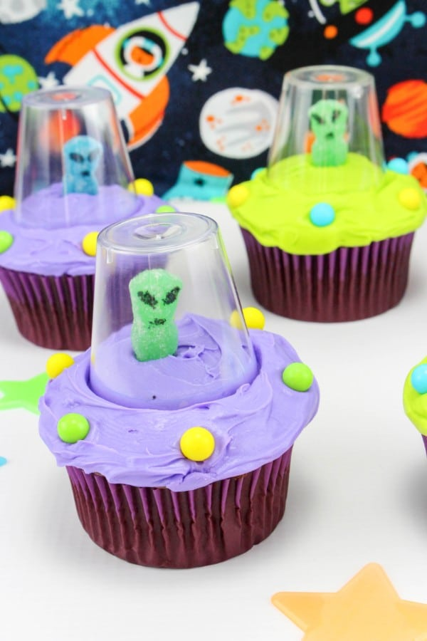 three cupcakes decorated with green or purple frosting, round candy, a gummy candy with eyes and a mouth drawn on with a plastic cup around it, on a white table with colored stars on it with a space scene in the background