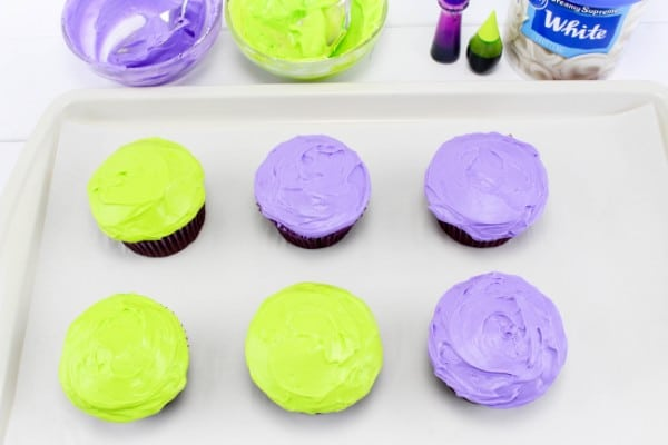 six cupcakes decorated with green or purple frosting on a white tray with bowls of frosting, food coloring, and white icing behind it, all on a white wood table
