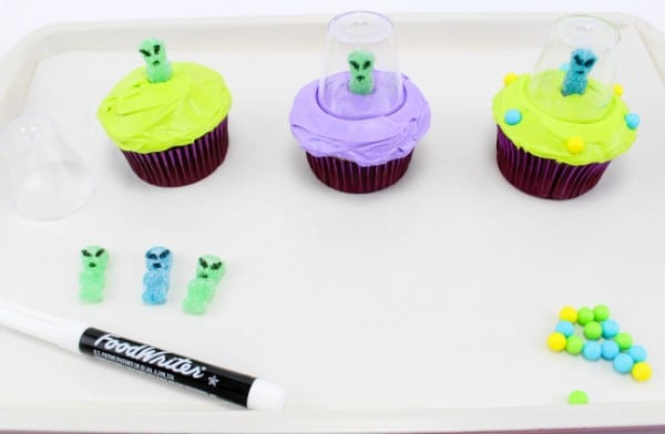 three cupcakes in various stages of being decorated with green or purple frosting, round candy, a gummy candy with eyes and a mouth drawn on with a plastic cup around it, on a white tray on a white table with the rest of the decorating ingredients on the tray