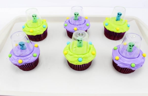six cupcakes decorated with green or purple frosting, round candy, a gummy candy with eyes and a mouth drawn on with a plastic cup around it, on a white tray on a white table