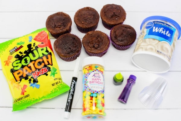 a bag of sour patch kids candy, six chocolate cupcakes, a container of white frosting, a black food marker, a container of round candy, two jars of green and purple food coloring, clear plastic cups, all on a white wood table