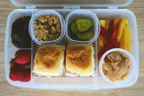 a plastic lunchbox full of strawberries, chocolate hummus, cashews, sliced pickles, two sliders, pepper strips and red pepper hummus on a brown table