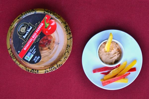 a container of roasted red pepper hummus next to a small bowl of hummus on a plate with some pepper slices, all on a red background