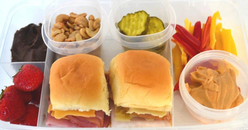 a divided plastic box with two sandwich sliders, strawberries and chocolate dip, cashews, pickles, red and yellow pepper slices, hummus