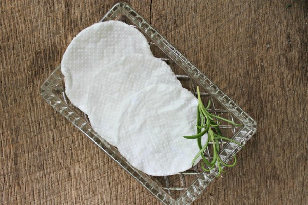 three makeup wipes on a glass tray with a green sprig on it, on a brown table