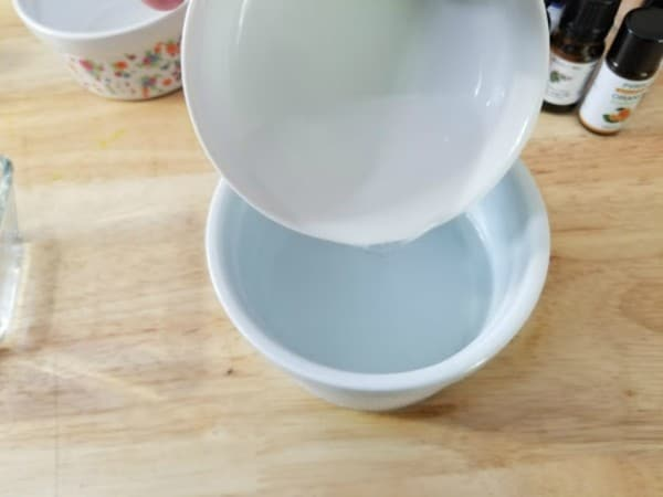 adding soap from a bowl to a bowl of distilled water on a brown table with more bowls and bottles in the background