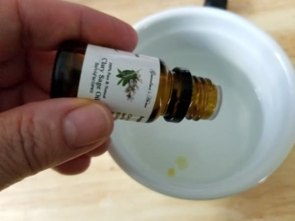 a hand pouring clary sage oil to a white bowl of soap, water and witch hazel on a wood table