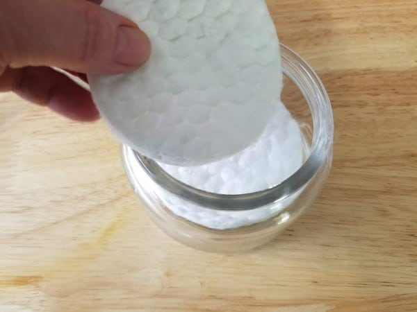 a hand putting cosmetic pads in a glass jar on a brown table