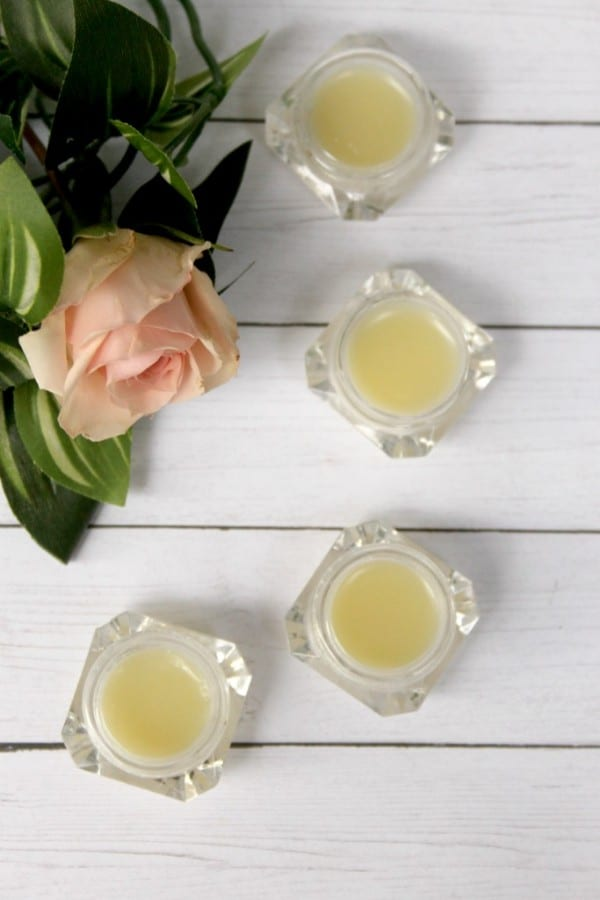 four jars of homemade eye cream on a white wood table with a flower in the background
