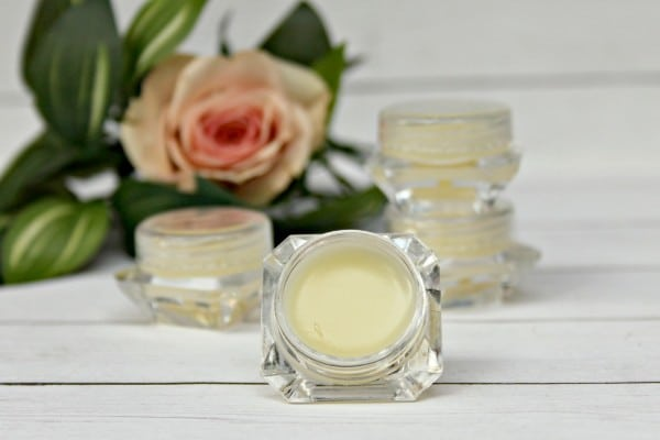 homemade eye cream in a jar on a white wood table with more jars and a flower in the background