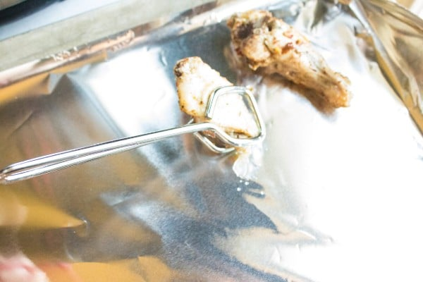 using a tong to place chicken wings on a foil lined baking sheet