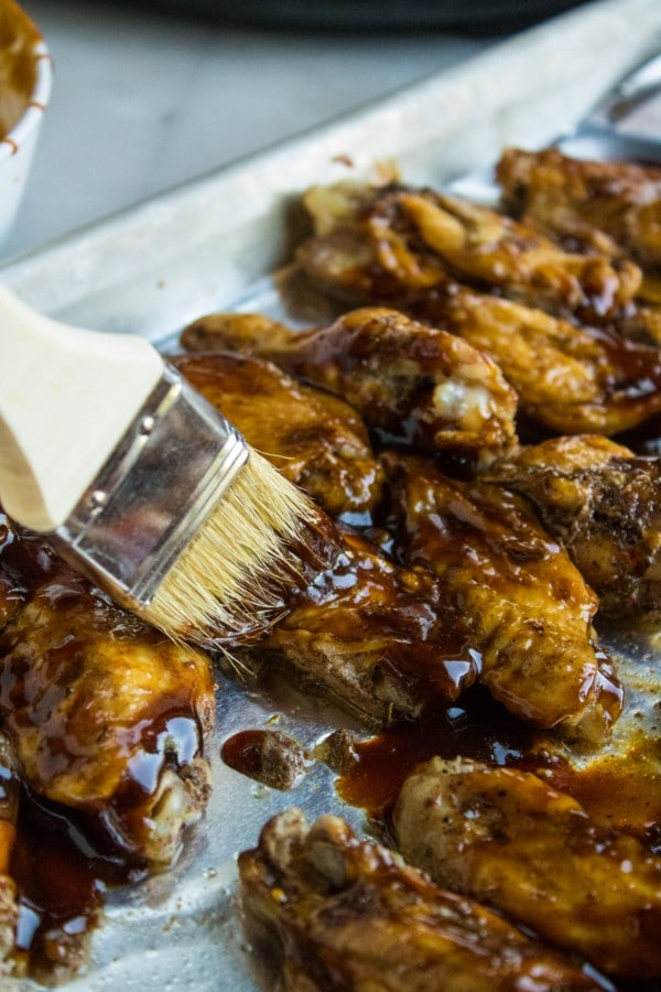 using a brush to spread sauce on chicken wings on a foil lined baking sheet