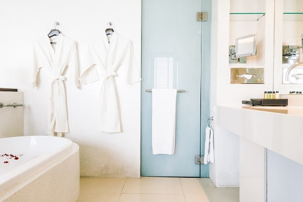 a white bathroom with a bathtub, counter, robes hanging on the wall