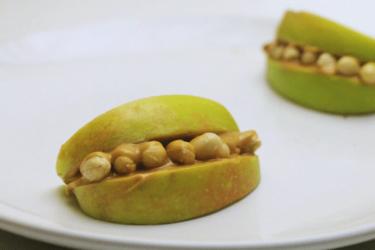 apple slices, peanut butter and peanuts decorated to look like a monster mouth on a white plate