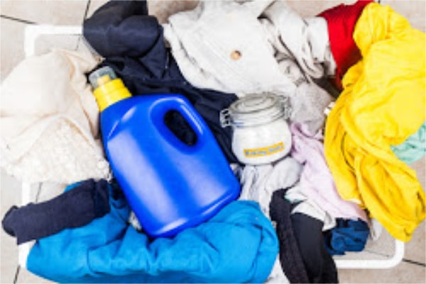 a laundry basket full of clothes with a plastic container of detergent on top and also a glass jar of baking soda