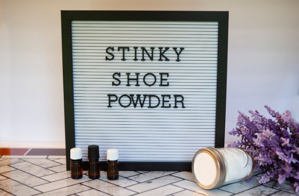 a sign with letters on it that reads Stinky Shoe Powder on a tile floor with bottles of essential oil, a jar of show powder, and lavender in front of it
