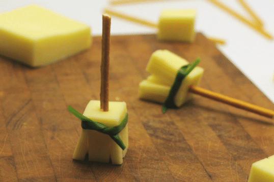 cheese with a pretzel stick stuck in the middle and a green tie around the cheese to look like a broomstick on a brown cutting board with more cheese and treats being assembled in the background